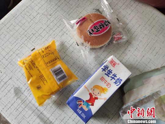 营养餐包括一小袋蛋糕、饼干和一瓶200毫升的牛奶,每个学生都有一份。 王昊昊 摄