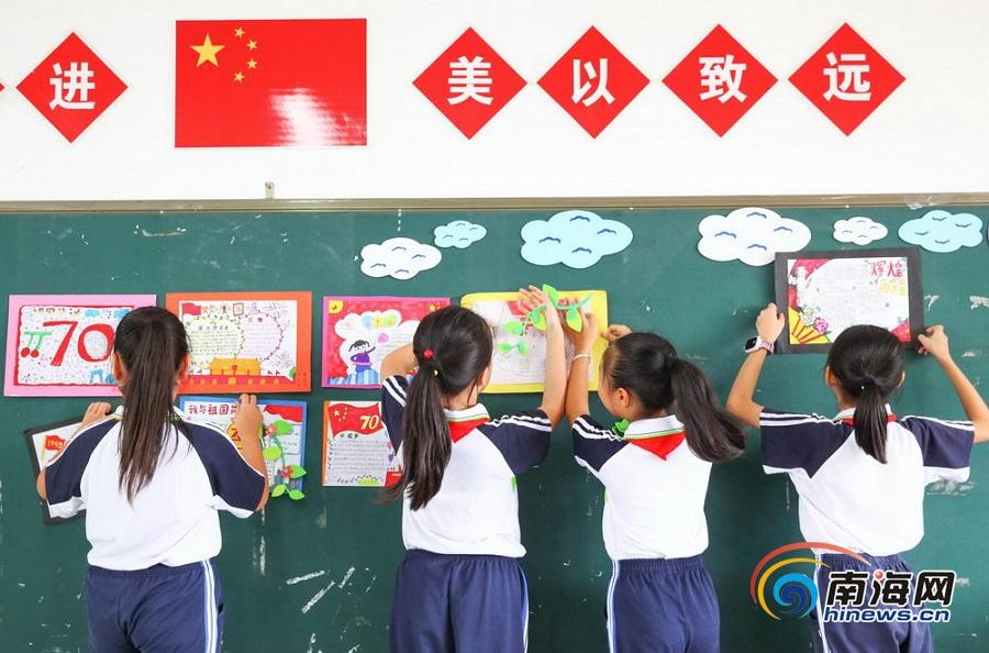 """南海网、南海网客户端海口9月25日消息(海报集团全媒体中心记者 张茂)为迎接新中国成立70周年,海口市第二十五小学开展以""""庆七十华诞 和美同行""""为主题的黑板报活动,该校四(6)班的学生们在利用课后时间将自己关于国庆主题的手抄报贴在黑板上。"""