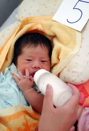可爱的宝宝正在吮吸着可口的牛奶,却不明白身边发生的一切