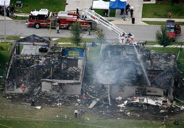 7月10日,美国救援人员正在飞机坠毁现场灭火.现场一片狼藉.