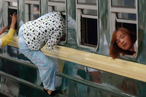 各地火车站迎来客流高峰 女乘客争爬火车