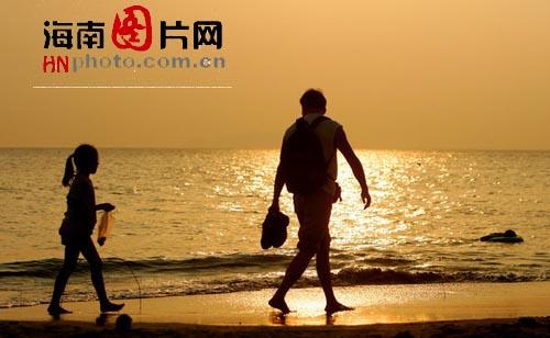 父女�ykd9il�i�9.ly/)_夕阳西下,一对父女在沙滩上散步看夕阳.