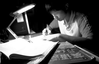 昨晚,一名学生在家里写作业-开学前 暑假作业枪手 忙 日赚数百元