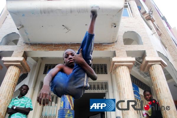 图为11岁的理查德正在展示自己的绝活,他就像蛇一样盘在一个窄小的塑料柱子上。(AFP/国际在线)   国际在线专稿:据法新社9月15日报道,在民主刚果首都金沙萨的街头,有一群靠表演柔术生活的人。他们每个月能赚到300美元左右(约合2483元人民币),这笔钱被他们用来支付学费,或者供养他们的家人。民主刚果缺乏必要的基础设施,让这些孩子们在体育馆里训练他们的特长。(Zak)