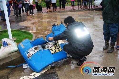 三轮车被撞瞬间遭神秘转移_交警正在清理农用三轮车被撞散的零件(南海网记者冯丹摄)