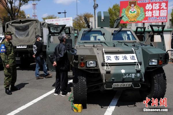 """日本自卫队军乐队举行""""我爱福岛""""主题演奏会,停在小广场一侧的救灾"""