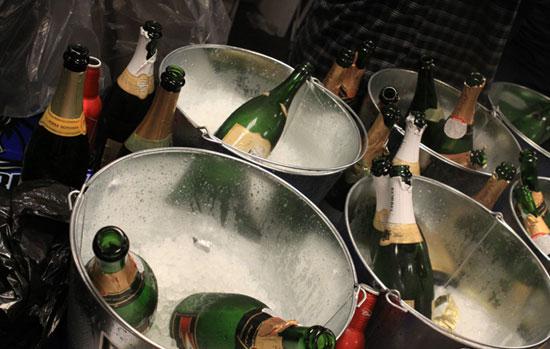满桌子的香槟瓶子和啤酒瓶成为主角,每人有一件总冠军t恤和帽子为荣.图片