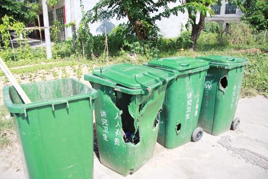 """图为被人为烧坏和砍坏的环保垃圾收集箱。记者 黎有科 摄   儋州新闻中心消息 近日,记者从市环卫局获悉,环卫部门去年下半年在那大城区投放约5000个密闭式环保垃圾收集箱,然而至今,却被人为毁坏300余个。   记者走访查看了人民东路、园地路等路段垃圾箱情况,在街上看到很多环保垃圾收集箱不是缺了盖子,就是少了""""兄弟"""",鲜有完整的。被人为毁坏的垃圾箱也不少,有的被人酒后踢坏,有的被砍坏,有的被人丢进燃烧后尚发热的煤球所烧坏。据介绍,每个垃圾箱政府采购价是480元。   市环卫局相关"""