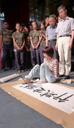 """李智华/李智华用脚夹着毛笔书写了""""励志践行""""四个大字,激励同学们。..."""