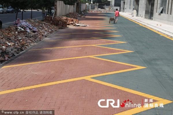 """""""地砖""""是不规则的形状,靠马路的一半是红色,划有70个停车位,用的是"""""""