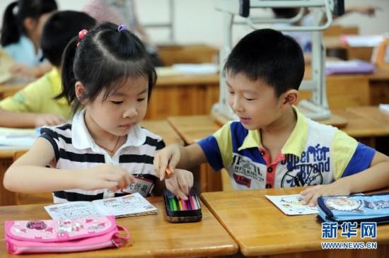 位8点多到校的小学生在画画,还未到校的学生的凳子叠放在桌子上