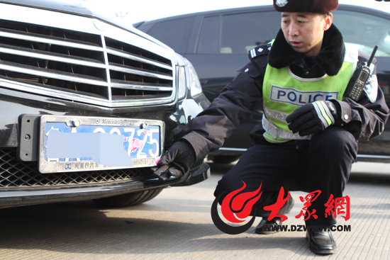 今天上午,一辆黑色奔驰车因前车牌被遮挡被交警拦下,驾驶员被记12分