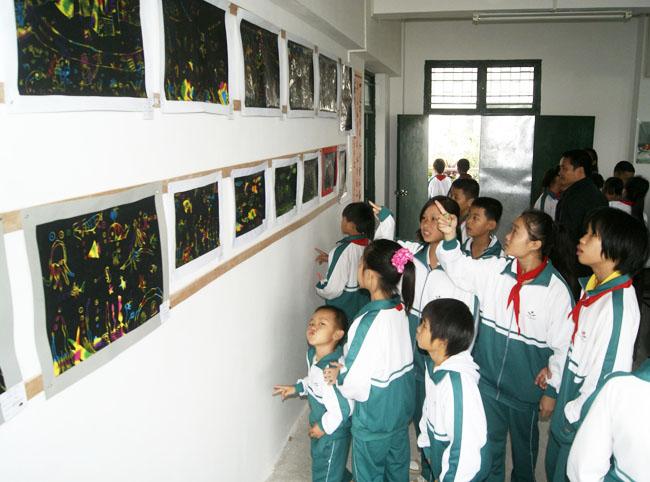 学生们在在作品展示厅欣赏挂在墙上的书画作品.