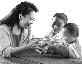 2006年,彭丽媛在安徽省阜阳市与艾滋病患儿做游戏。