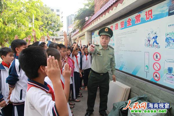 在安全宣传展板前,民警组织开展校园交通安全提问