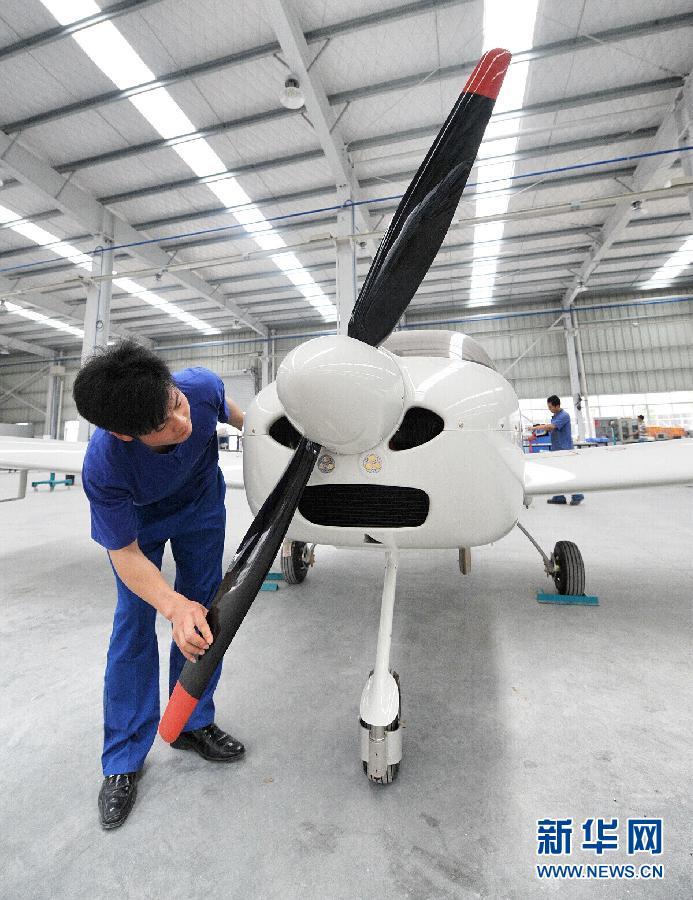 """5月16日 湖南产轻型运动飞机获民航局""""准生证"""" 一名工人在山河科技生产厂房内组装""""阿诺拉""""轻型运动飞机(5月15日摄)。   近日,位于湖南省株洲市的湖南山河科技股份有限公司正式获颁中国第一个全自主研制的全复合材料轻型运动飞机生产许可认证,这是中国民航第一次为国内自主品牌通航制造企业颁发该类型飞机的生产许可证,标志着中国从此拥有了真正属于自己的民用轻型运动飞机批量生产基地。据介绍,获得生产许可证后,山河科技产的""""阿诺拉""""SA6"""