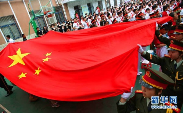 6月6日,国旗班老班长和小学生共同传递五星红旗.(新华网发王超摄)