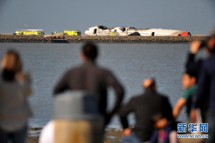 7月6日,在美国加利福尼亚州旧金山,人们远望失事飞机残骸。韩国亚洲航空公司一架波音777-200型客机6日在美国旧金山国际机场降落过程中发生事故,燃起大火。新华社记者7日从韩国国土交通部得到证实,韩亚航空失事航班上遇难的两名乘客均为中国公民。新华社发(刘艺霖摄)
