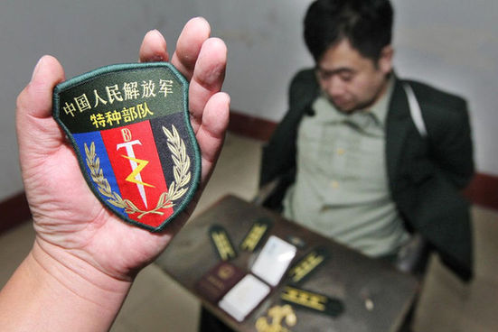 """苍山县公安局审讯室内,民警向记者展示""""特种部队""""的臂章."""