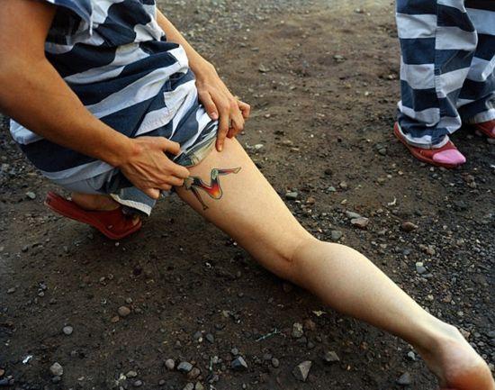 镣铐枷锁女犯-一位女囚向休斯顿展示其腿上的刺青-揭秘美国女子重囚监狱 手铐脚镣图片
