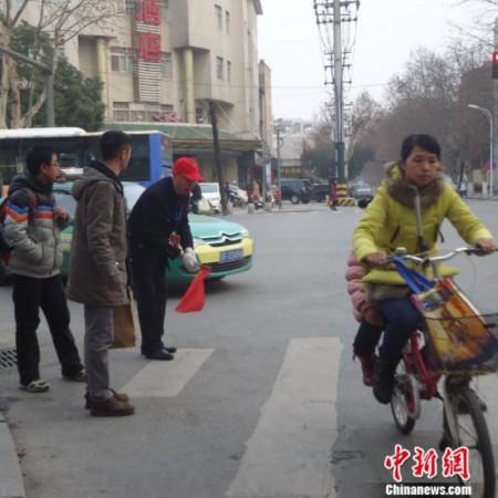 """湖北襄阳六旬老人鞠躬劝阻""""中国式过马路""""(图)"""