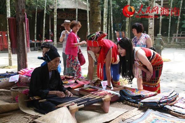 文薇与主持人观看黎族文身阿婆编织黎锦图片