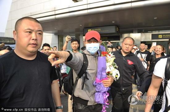 组图:刘德华口罩遮面现身机场 仍遭粉丝围堵