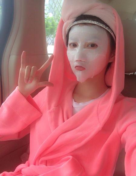 照片中景甜身粉色浴袍,坐在皮椅上淡定敷面膜,右手还摆出可爱pose