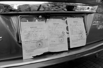 小轿车引起过往市民的围观.这辆车的号牌上贴了3张罚单,轿车高清图片