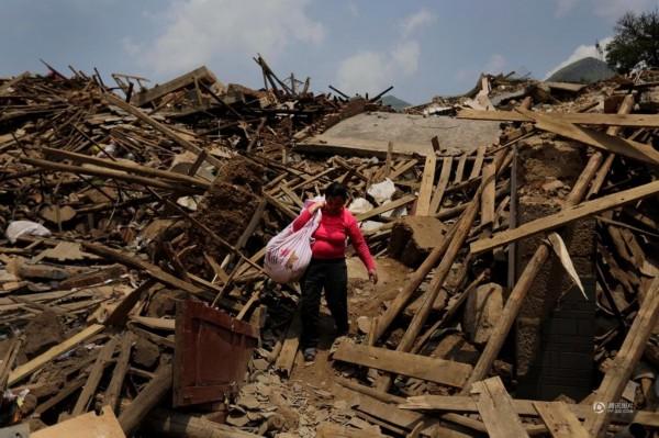8月6日,云南鲁甸龙头山镇,妇女在废墟中收集着可用的家用物品.-图片