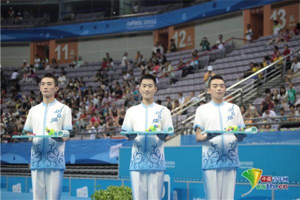 南京奥体中心进行的男子蹦床比赛颁奖礼仪。中国青年网记者黄威摄 中国青年网南京8月22日电(记者黄威)今日下午,南京奥体中心进行了男子蹦床比赛,场上运动员动作飘逸、表现精彩,场下观众充满激情。此次蹦床比赛的颁奖现场,是由三位男礼仪替代了以往的女礼仪,展示出了男性之美。