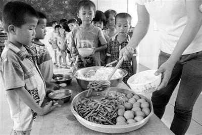 幼儿园生活老师给孩子打饭.