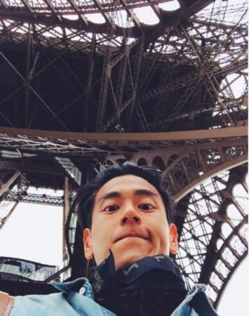 照片中,彭于晏站在埃菲尔铁塔下低头自拍,抿嘴造型十分帅气可爱.