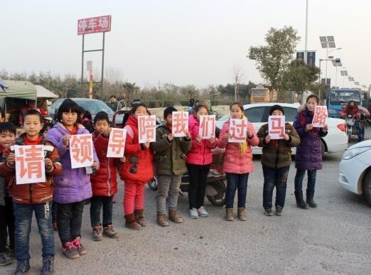 图片说明:学生排队过马路-郑州一路口无红绿灯 小学生举牌请领导陪走