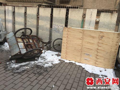废弃的车子和木板在人行道上随意丢弃
