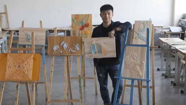 1994年出生的蔡孙翔,目前是长春大学旅游学院一名大三的学生,戏剧影视美术设计专业。从高中开始学习画画的他,对手工制作也是情有独钟。有一种叫String Art的艺术,先在木板上钉上钉子,然后用线绕出图案。而东阳小伙蔡孙翔喜欢更直接地称之为钉子画。图为蔡孙翔和自己的作品。