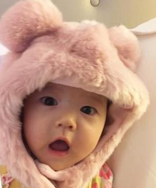 """""""照片中小宝贝头戴粉色小熊绒帽,对着镜头毫不怯场,时而大眼呆萌,时而"""