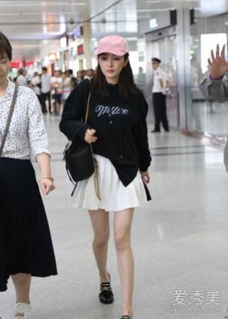 杨幂用黑色卫衣配白色小短裙,百褶裙很有学生气息,加上粉色棒球
