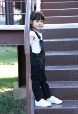 其中一组黑白系的照片中孙梦晗身穿白色t恤搭配黑色背带裤,乖巧可爱.