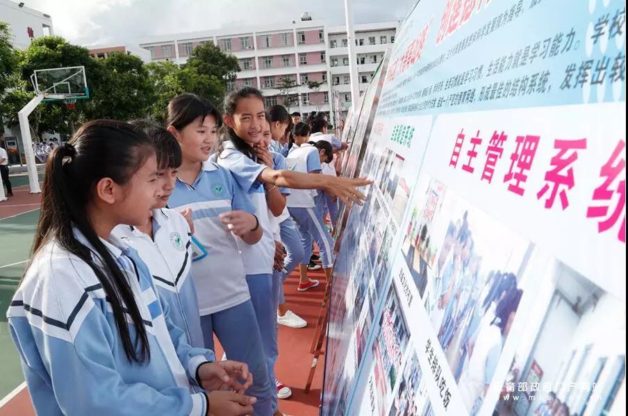 海南陵水思源实验学校操场上,同学们正在观看学校宣传展板张劲松摄