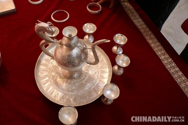 勒古沙日纯手工制作的银质酒壶。(中国日报网 贺霞婷 摄)   勒古沙日家族是银匠世家,到他已经是第15代传承人,如今的他,除了制作这些精巧的银器外,还花费了大量的精力在传承这门手艺,不仅教他的儿子和孙子还教布拖县的很多年轻人学习这门手艺。   现场,勒古沙日用一个银质酒壶给记者倒上了满满的一碗酒。酒壶造型别致,纹路繁复,总共有32个部位,所有的点刻,组装都由他一个人完成。勒古沙日告诉记者,自己是整个四川省唯一能够纯手工打造这个银制酒壶的人。